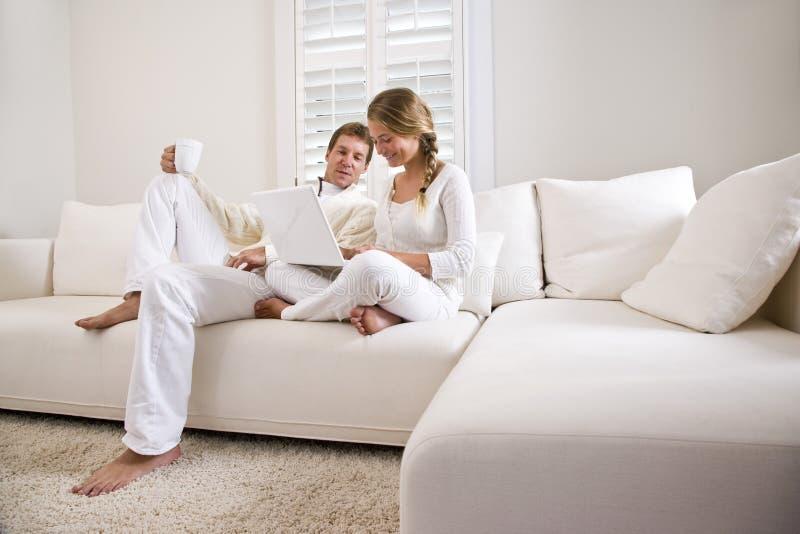 Padre e hija adolescente en el sofá blanco con la computadora portátil fotos de archivo