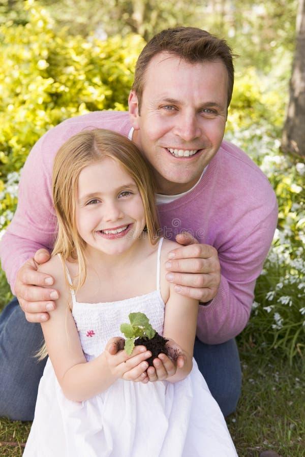 Padre e hija al aire libre que celebran la sonrisa de la planta fotos de archivo libres de regalías