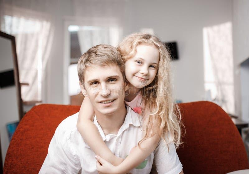 Padre e hija alegres felices junto en el sofá rojo en casa imagenes de archivo
