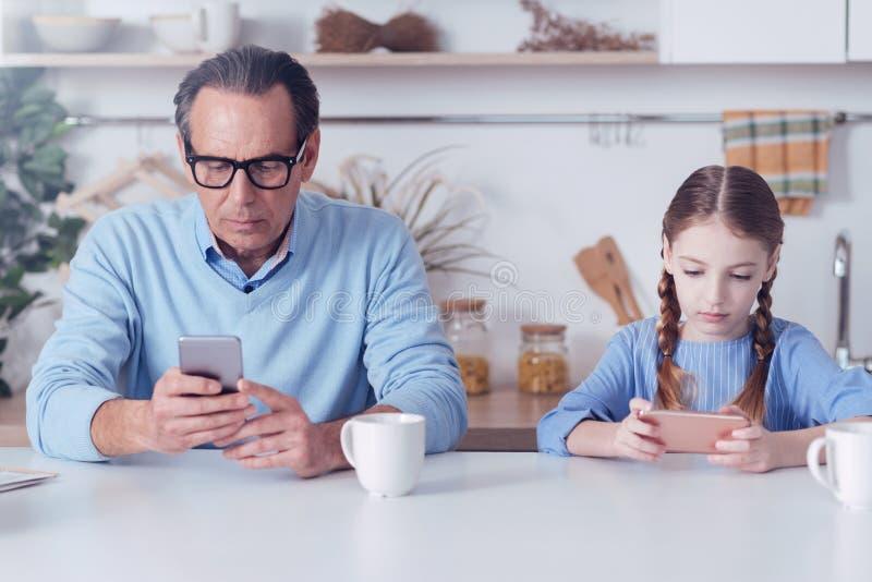 Padre e hija apuestos serios que usa sus smartphones fotografía de archivo