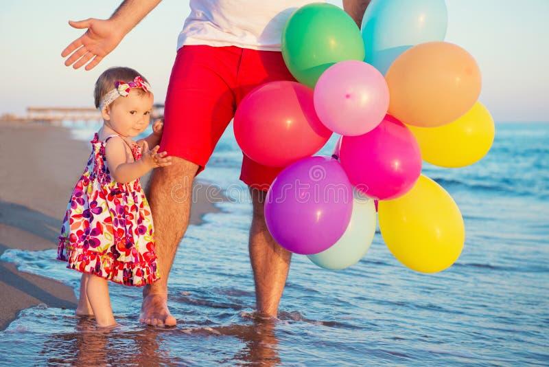 Padre e hija con los globos que juegan en la playa en el tiempo del día Concepto de familia amistosa foto de archivo libre de regalías