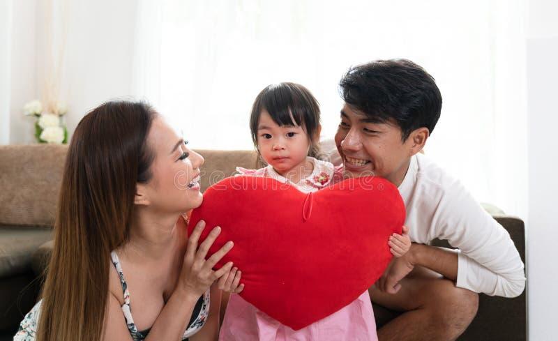 Padre e hija de la madre que sostienen la almohada del corazón fotos de archivo libres de regalías