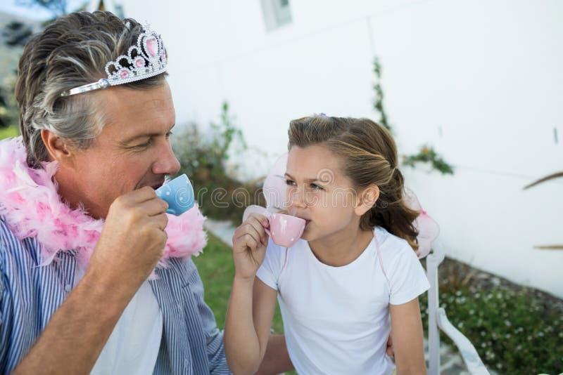 Padre e hija en el traje de hadas que tiene una fiesta del té imagen de archivo