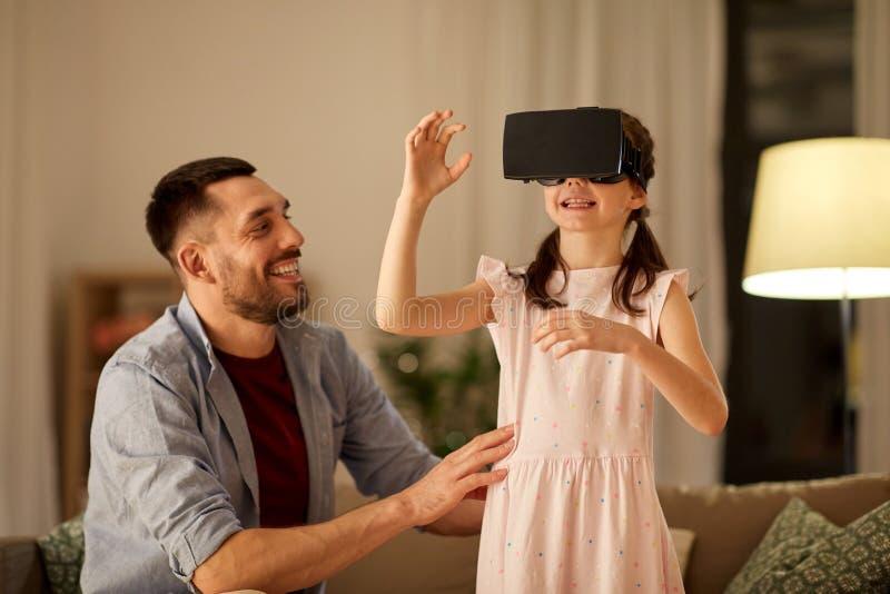 Padre e hija en los vidrios del vr que juegan en casa imagen de archivo libre de regalías