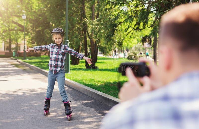 Padre e hija en pcteres de ruedas y casco imagen de archivo libre de regalías