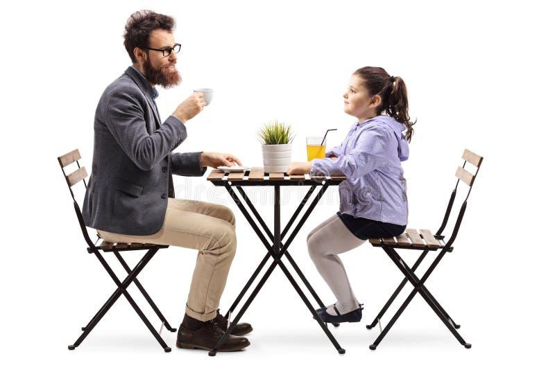Padre e hija en un café de la cafetería y un zumo de naranja de consumición fotos de archivo