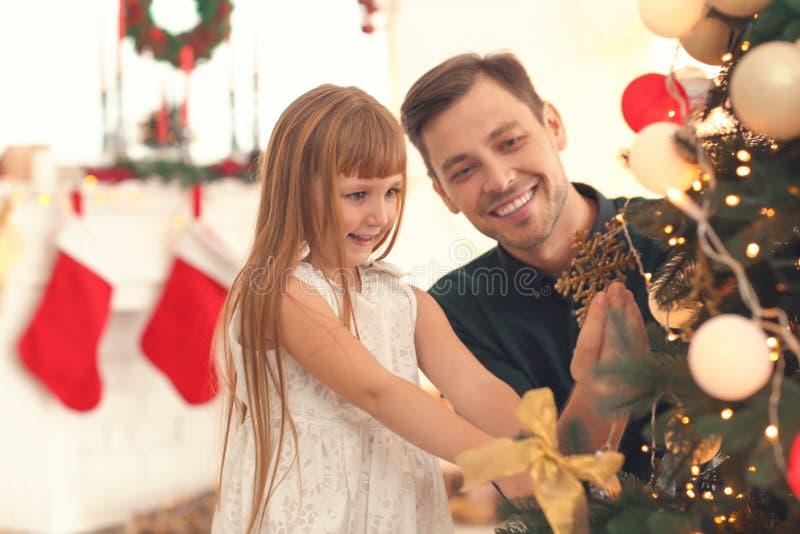 Padre e hija que adornan el árbol de navidad hermoso en sitio fotografía de archivo