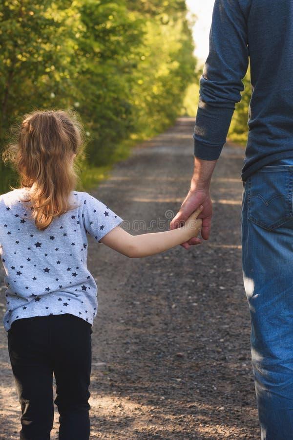 Padre e hija que caminan en el parque que lleva a cabo las manos Amaremos y tomaremos a cuidado de usted para siempre concepto fotografía de archivo