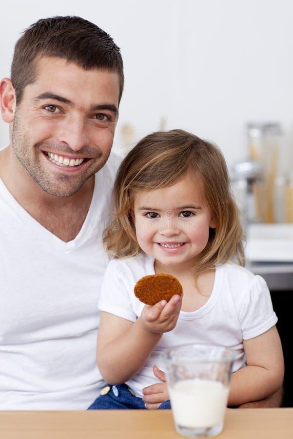 Padre e hija que comen las galletas con leche imagenes de archivo
