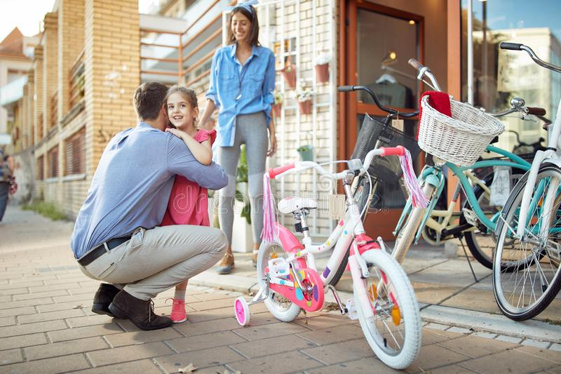 Padre e hija que compran la nueva bicicleta en tienda de la bici imagen de archivo