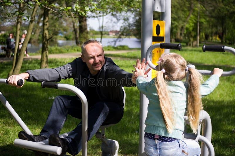 Padre e hija que ejercitan al aire libre fotografía de archivo