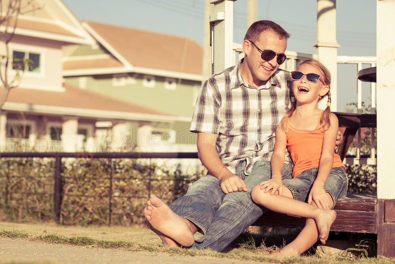 Padre e hija que juegan cerca de la casa en el tiempo del día imagen de archivo libre de regalías