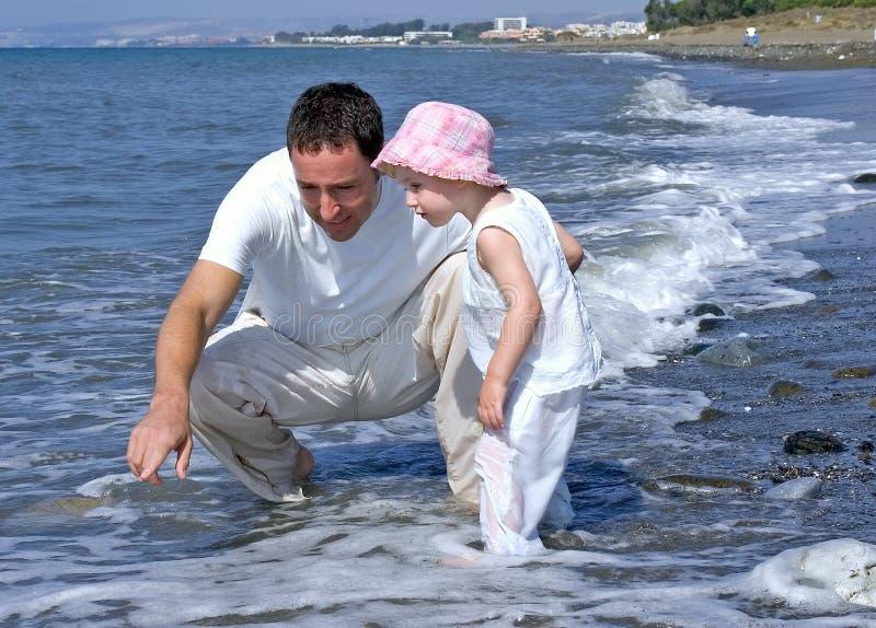 Padre e hija que juegan en el mar fotografía de archivo libre de regalías