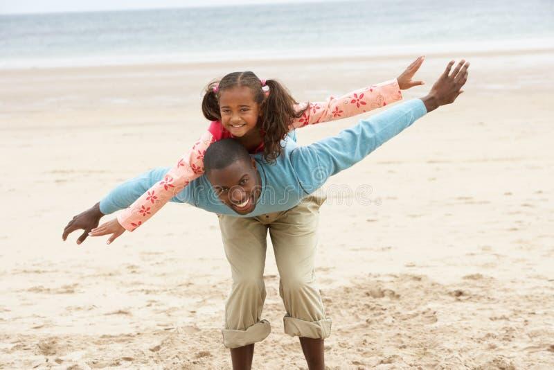 Padre e hija que juegan en la playa fotografía de archivo