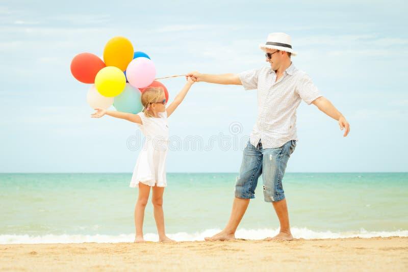 Padre e hija que juegan en la playa en el tiempo del día imagen de archivo libre de regalías
