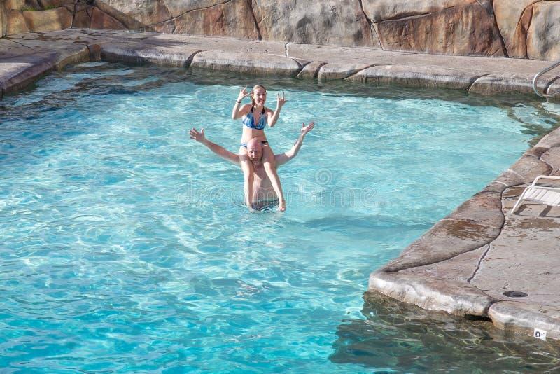 Padre e hija que juegan en piscina fotografía de archivo