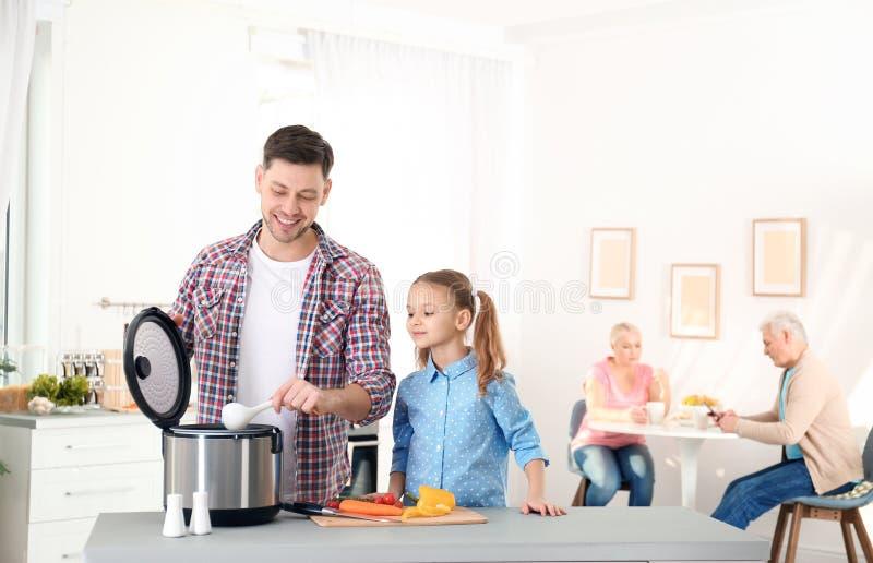 Padre e hija que preparan la comida con la cocina multi moderna foto de archivo