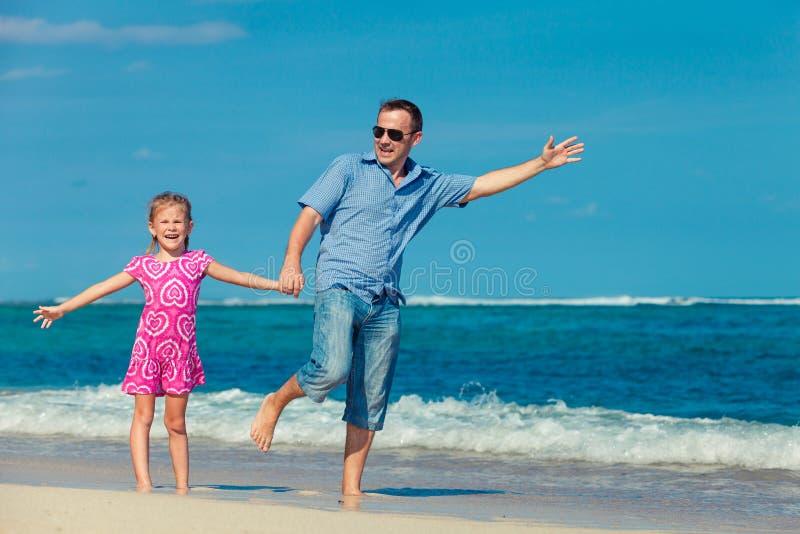 Padre e hija que se colocan en la playa fotografía de archivo