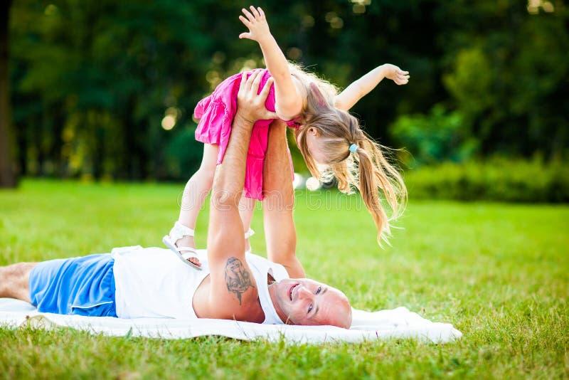 Padre e hija que se divierten en un parque fotografía de archivo libre de regalías