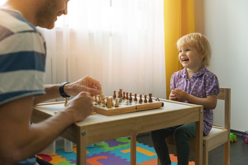 padre e hija que se divierten junto que aprende jugar a ajedrez fotografía de archivo