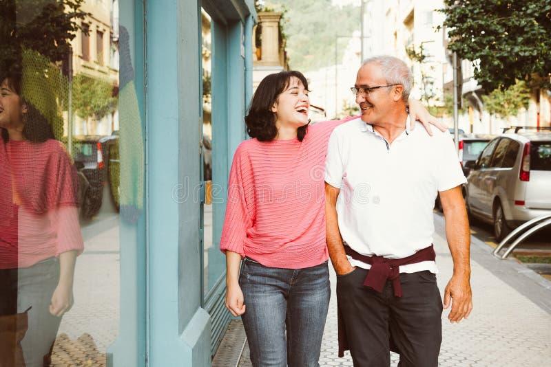 Padre e hija que se divierten junto que camina en la calle imagenes de archivo