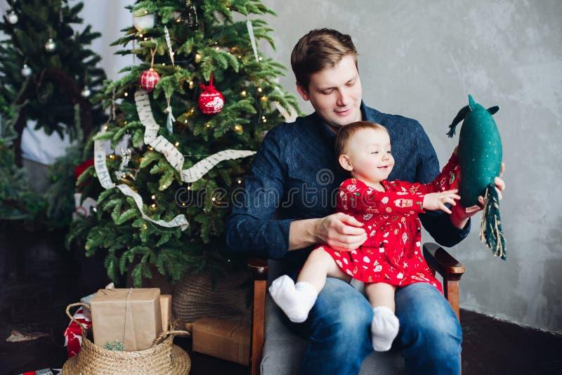 Padre e hija que se sientan en el sofá debajo de la guirnalda grande del abeto fotos de archivo libres de regalías