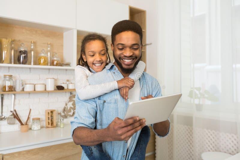 Padre e hija que tienen llamada video en la tableta en cocina fotografía de archivo
