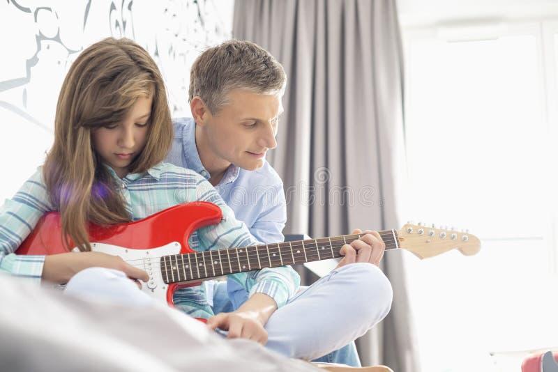 Padre e hija que tocan la guitarra eléctrica en casa foto de archivo