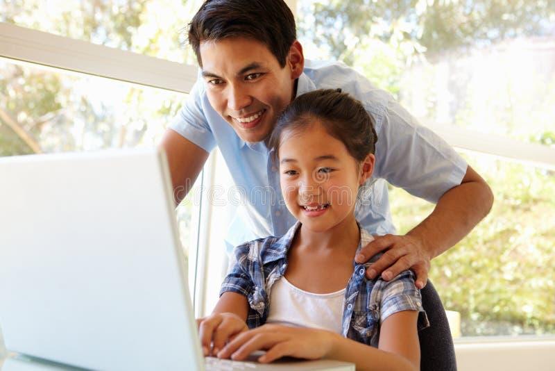 Padre e hija que usa la computadora portátil foto de archivo