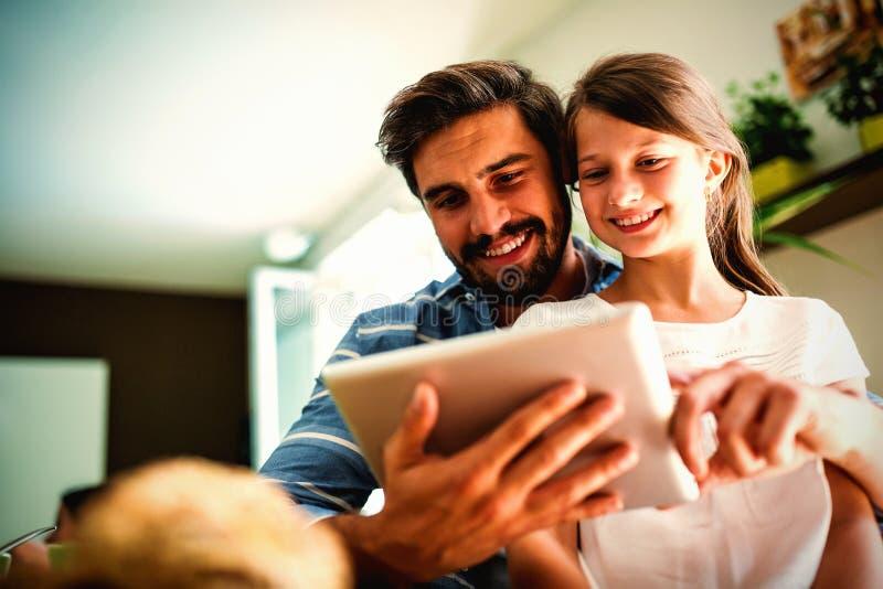 Padre e hija que usa la tableta digital en la sala de estar fotografía de archivo