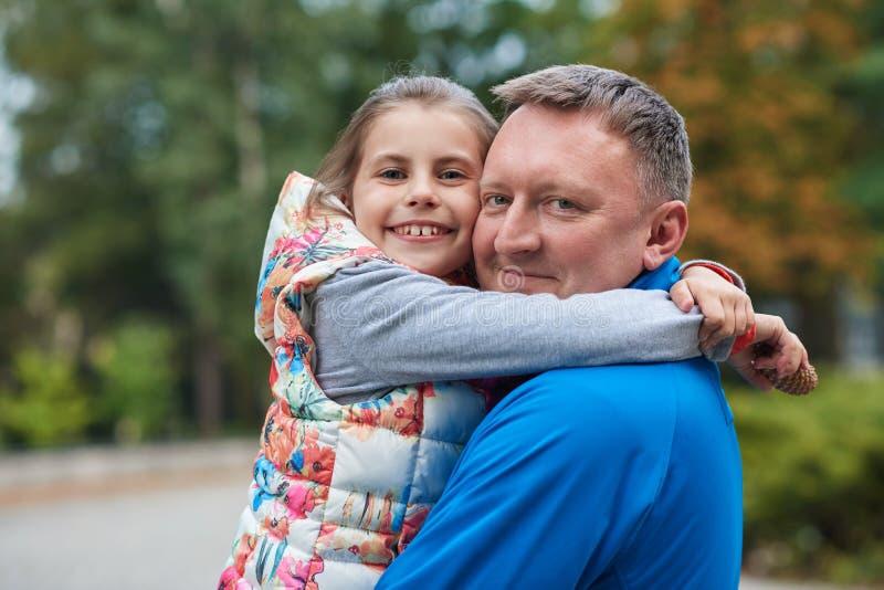 Padre e hija sonrientes que abrazan en un parque imagen de archivo