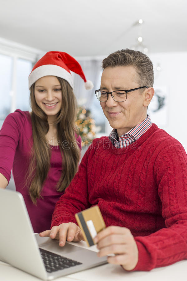 Padre e hija sonrientes que hacen compras en línea en casa durante la Navidad fotos de archivo