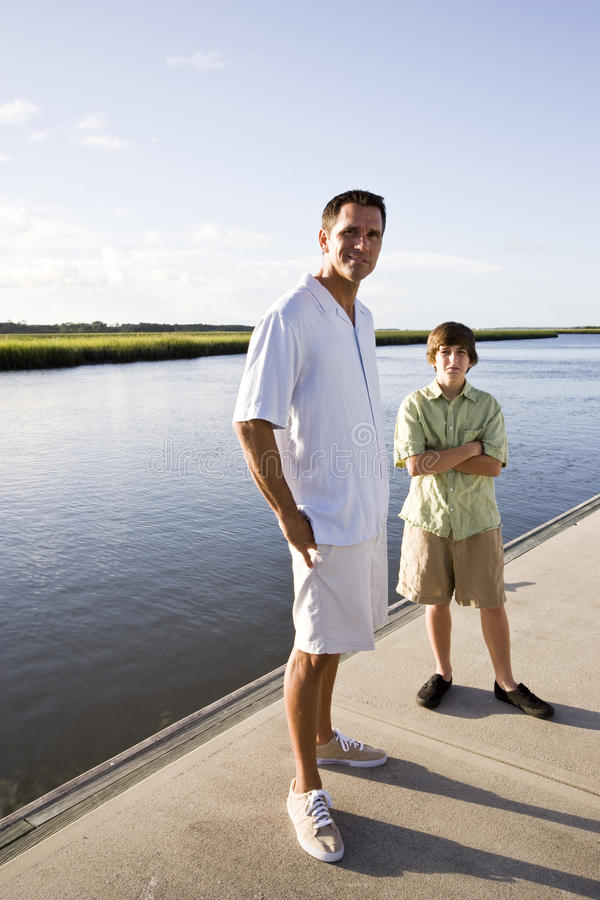 Padre e hijo adolescente que defienden en muelle el agua foto de archivo libre de regalías