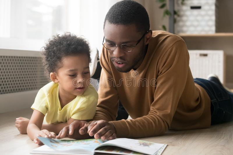 Padre e hijo afroamericano leyendo juntos un libro imagenes de archivo