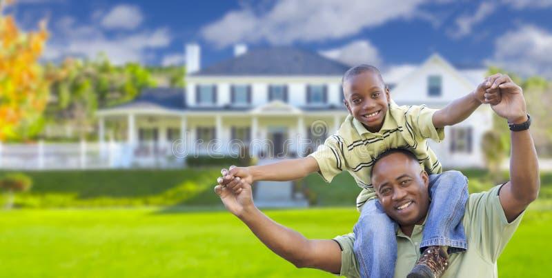Padre e hijo afroamericanos juguetones delante del hogar imagen de archivo