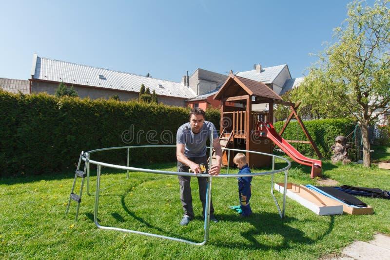 Padre e hijo al instalar los trampolines grandes del jardín imágenes de archivo libres de regalías