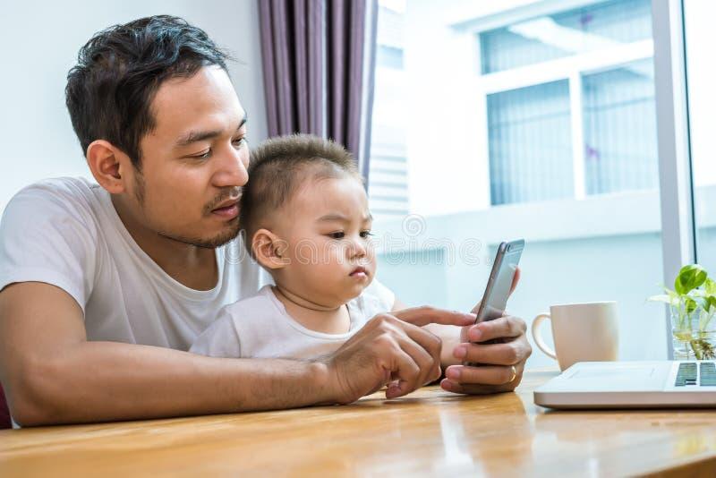 Padre e hijo asiáticos que usa el teléfono elegante junto en el fondo casero Concepto de la tecnología y de la gente Formas de vi imágenes de archivo libres de regalías