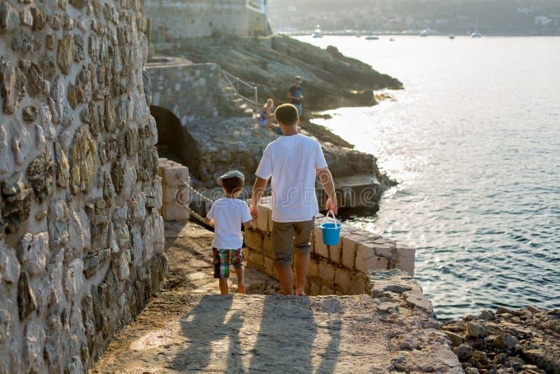 Padre e hijo, caminando de común acuerdo en una trayectoria de la costa de mar foto de archivo