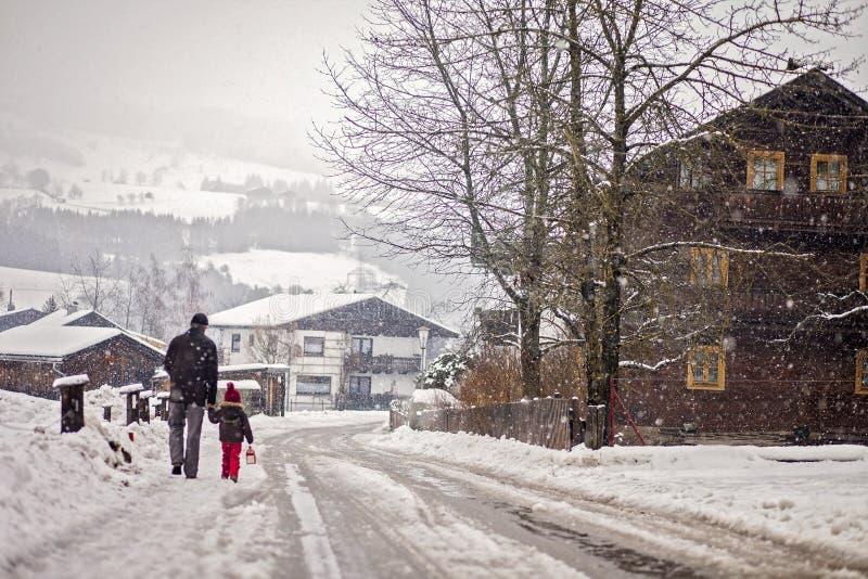 Padre e hijo, caminando en el día nevoso en un pueblo fotografía de archivo