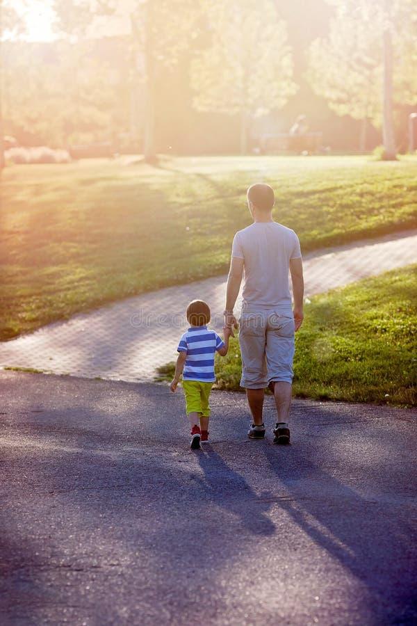 Padre e hijo, caminando en un parque en puesta del sol, concepto del día de padres foto de archivo