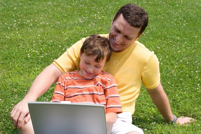 Padre e hijo con la computadora portátil imágenes de archivo libres de regalías