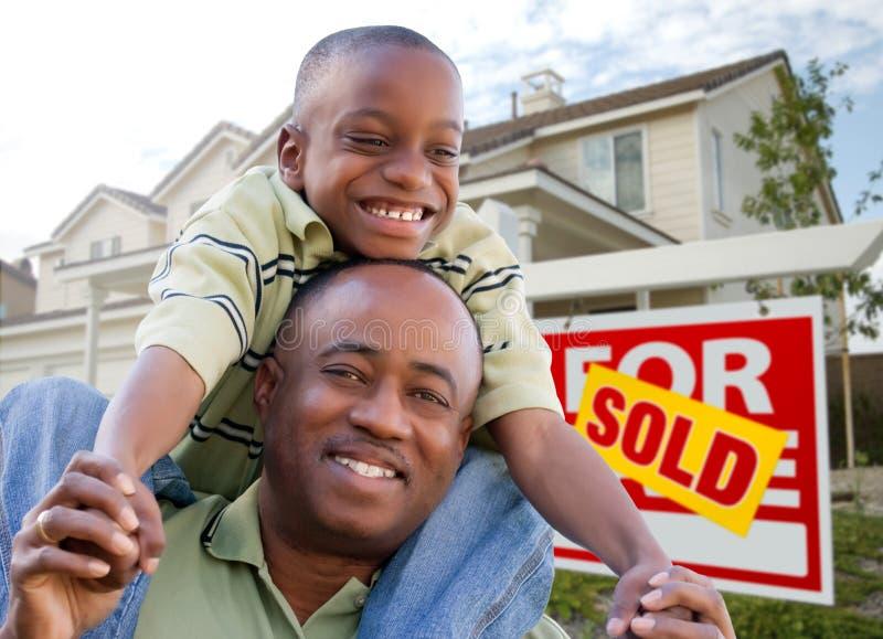 Padre e hijo con la muestra y el hogar de las propiedades inmobiliarias foto de archivo libre de regalías