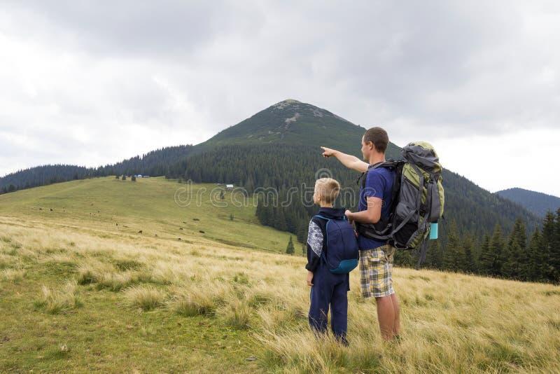 Padre e hijo con las mochilas que caminan junto en montañas del verano Opinión trasera el papá y el niño que llevan a cabo las ma foto de archivo libre de regalías