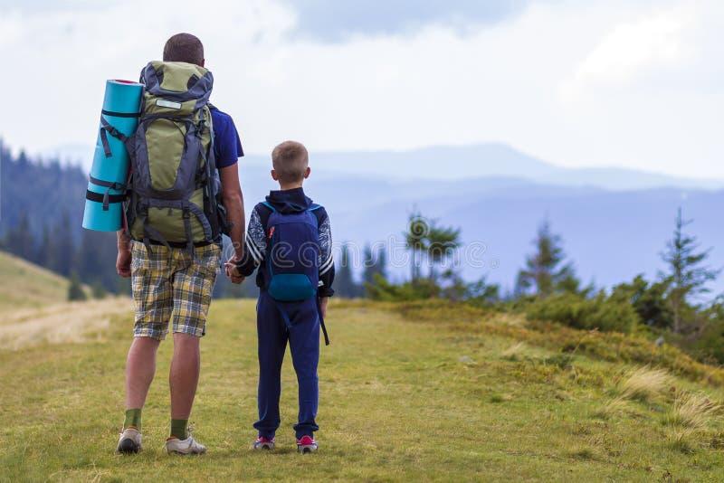 Padre e hijo con las mochilas que caminan junto en montañas escénicas del verde del verano Papá y niño que se colocan de goce de  fotografía de archivo libre de regalías