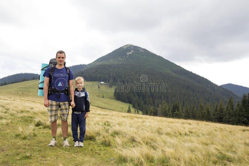 Padre e hijo con las mochilas que caminan junto en monta?as del verano Papá y niño que llevan a cabo las manos en Mountain View d fotos de archivo libres de regalías
