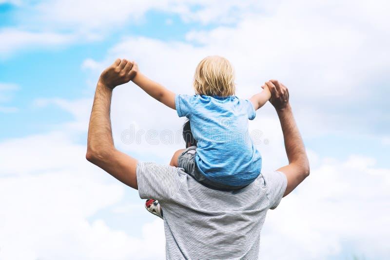 Padre e hijo con los brazos aumentados para arriba contra el cielo fotografía de archivo libre de regalías