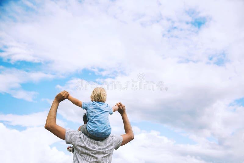 Padre e hijo con los brazos aumentados para arriba contra el cielo fotografía de archivo