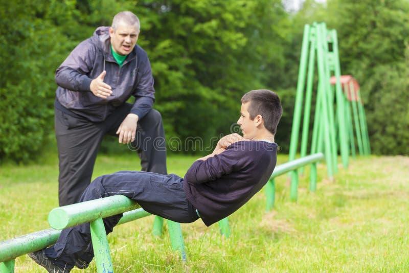 Padre e hijo contratados a ejercicios atléticos imagen de archivo