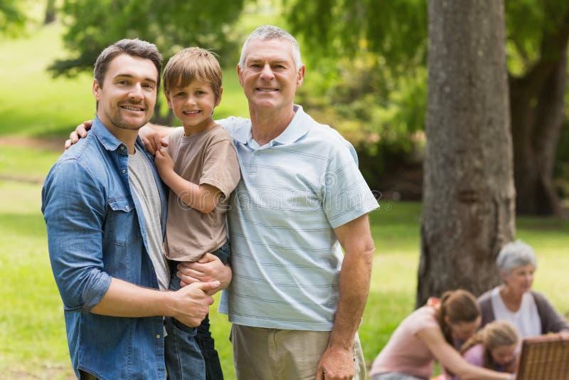 Padre e hijo de abuelo con la familia en fondo en el parque imagen de archivo