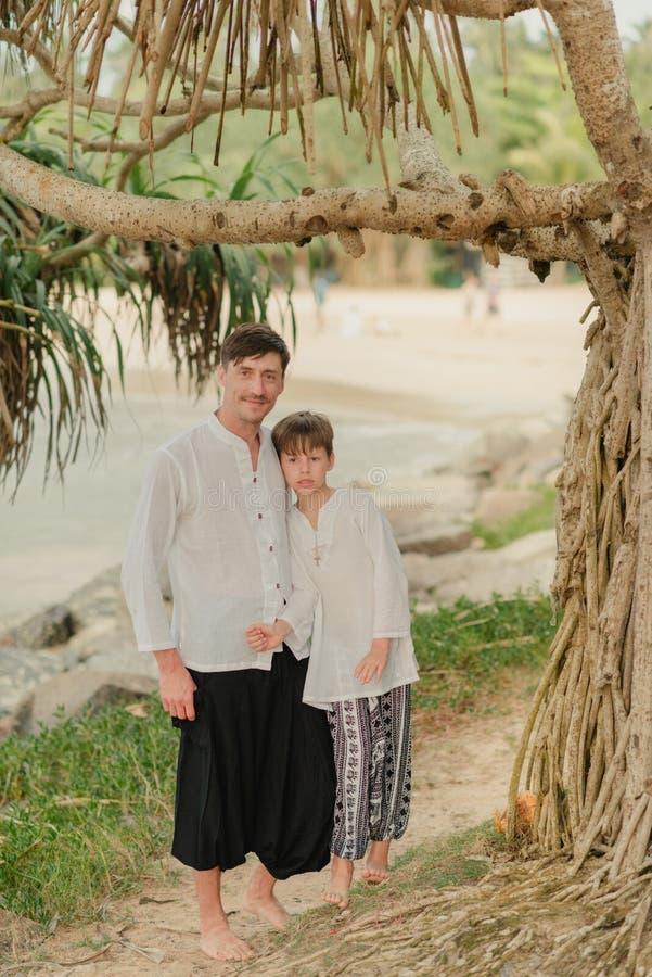 Padre e hijo debajo de un árbol en los pantalones indios imagen de archivo libre de regalías